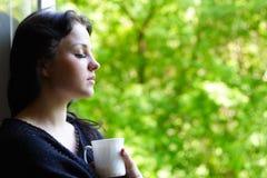 Mooi meisje met een mok koffie Stock Afbeeldingen