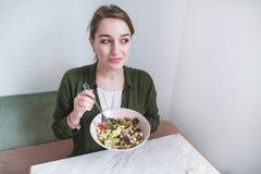 mooi meisje met een plaat van salade in haar handen en een blik in de richting De vrouw eet gezond voedsel stock foto's