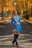 Mooi meisje met een zak in een korte kleding en beenkappen die langs de weg in de herfstpark lopen Stock Afbeelding