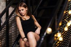 Mooi meisje met eerlijk haar die zwarte uitrustings stellende zitting op stappen van de trap van de metaalbrandtrap dragen royalty-vrije stock afbeeldingen