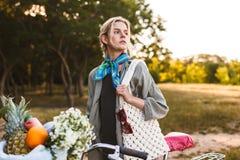 Mooi meisje met fiets en mandhoogtepunt van wildflowers en F royalty-vrije stock foto