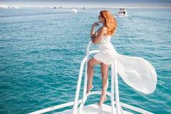 Mooi meisje met fladderende witte kleding en rood krullend haar die zich op kapiteins` s brug bevinden van jacht Royalty-vrije Stock Fotografie