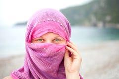 Mooi meisje met gezicht dat door rode sjaal wordt behandeld Stock Afbeeldingen