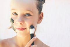 Mooi meisje met gezichts zwart kleimasker royalty-vrije stock foto's