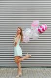 Mooi meisje met golvend haar met kleurenballons tegen gestreepte achtergrond Royalty-vrije Stock Fotografie