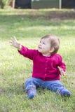 Mooi meisje met gras het in hand kijken omhooggaand en het glimlachen Royalty-vrije Stock Afbeelding