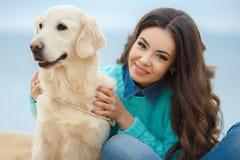 Mooi meisje met haar hond dichtbij overzees Royalty-vrije Stock Foto's