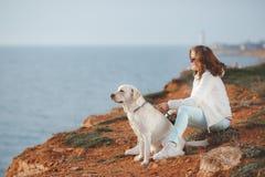 Mooi meisje met haar hond dichtbij overzees Royalty-vrije Stock Afbeeldingen