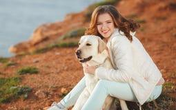 Mooi meisje met haar hond dichtbij overzees Royalty-vrije Stock Foto