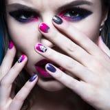 Mooi meisje met heldere creatieve maniermake-up en kleurrijk nagellak Het ontwerp van de kunstschoonheid Stock Foto's