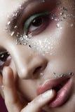Mooi meisje met heldere kleurenmake-up en kristallen op het gezicht De gelukkige jonge zakken van de meisjesholding op een witte  Royalty-vrije Stock Foto