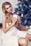 Mooi meisje met het blonde haar stellen naast een Kerstboom royalty-vrije stock afbeelding