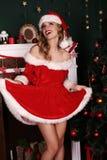 Mooi meisje met het blonde haar stellen naast Kerstboom stock afbeeldingen