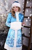 Mooi meisje met het blonde haar stellen naast Kerstboom stock afbeelding
