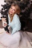 Mooi meisje met het blonde haar stellen naast Kerstboom royalty-vrije stock afbeeldingen