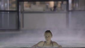 Mooi meisje met het perfecte lichaam zwemmen door de damp in de pool stock videobeelden