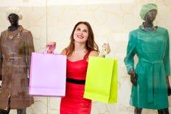 Mooi meisje met kleurrijke die pakketten in de opslag worden bewonderd Stock Foto's