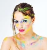 Mooi meisje met kleurrijke verfplonsen op gezicht Stock Afbeeldingen