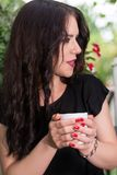 Mooi meisje met kop van koffie in en tuinpark die spreken ontspannen royalty-vrije stock afbeelding