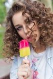 Mooi meisje met krullend met naakte sexy lippen die kleurenroomijs in een koffie in het park eten een heldere de zomerdag Stock Fotografie