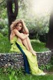 Mooi meisje met krullende haarzitting op het gras Royalty-vrije Stock Foto's