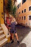 Mooi meisje met lang blond haar in het elegante kleding stellen in het Italiaans straat royalty-vrije stock foto
