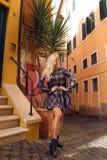 Mooi meisje met lang blond haar in het elegante kleding stellen in het Italiaans straat royalty-vrije stock afbeelding