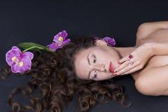 Mooi meisje met lang golvend haar op de vloer Royalty-vrije Stock Fotografie