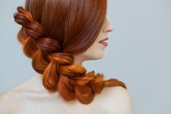 Mooi meisje met lang rood die haar, met een Franse vlecht, in een schoonheidssalon wordt gevlecht stock foto's