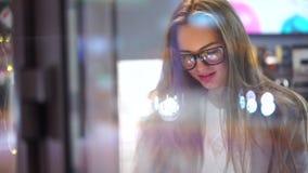 Mooi Meisje met lange haar en glazen die tablet gebruiken en mobiele telefoon in koffie 4 K stock video