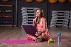 Mooi meisje met laptop Atleet met domoren die een telefoon op een vage achtergrond houden Actief levensstijlconcept royalty-vrije stock fotografie