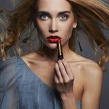 Mooi meisje met lippenstift jonge Vrouw die rode lippenstift zetten Stock Afbeelding