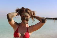 Mooi meisje met moddermasker Stock Afbeelding