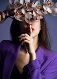 Mooi meisje met orchideebloemen Gezicht van de schoonheids het modelvrouw op purpere achtergrond stock afbeeldingen