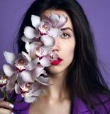 Mooi meisje met orchideebloemen Gezicht van de schoonheids het modelvrouw op purpere achtergrond royalty-vrije stock foto's