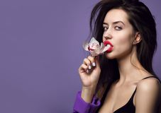 Mooi meisje met orchideebloemen Gezicht van de schoonheids het modelvrouw op purpere achtergrond stock foto