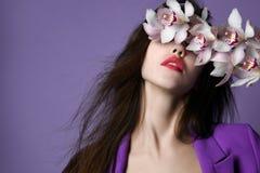 Mooi meisje met orchideebloemen Gezicht van de schoonheids het modelvrouw op purpere achtergrond stock foto's