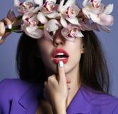 Mooi meisje met orchideebloemen Gezicht van de schoonheids het modelvrouw op purpere achtergrond royalty-vrije stock foto