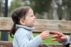 mooi meisje met paardestaarten en in een sweaterzitting op een bank in het park en het glimlachen royalty-vrije stock afbeelding