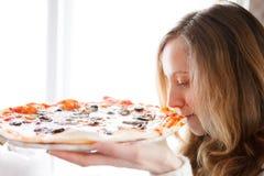 Mooi meisje met pizza. Geniet van de geur van vers gekookte pizza stock afbeelding