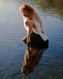 Mooi meisje met rood die haar in rimpelingen en nog water wordt weerspiegeld royalty-vrije stock foto's