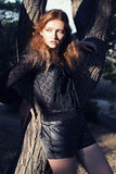 Mooi meisje met rood haar en sproeten die naast een boom stellen Stock Fotografie