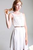 Mooi meisje met rood haar en sproeten in elegante witte kleding Royalty-vrije Stock Foto's