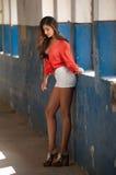 Mooi meisje met rood overhemd en witte borrels die in oude zaal stellen met geschilderde kolommenblauw Aantrekkelijk lang haarbru Stock Foto's
