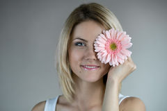Mooi meisje met roze bloem royalty-vrije stock afbeeldingen