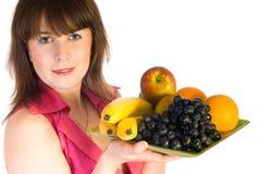 Mooi meisje met schotel van vruchten stock foto's