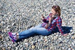 Mooi meisje met telefoonzitting op rotsachtig strand Stock Afbeeldingen