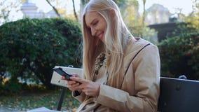 Mooi meisje in modieus jasje die smartphone in het park gebruiken bij zonnige dag in de herfstpark stock videobeelden