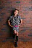 Mooi meisje in modieuze uitrusting met handen op heupen stock foto's