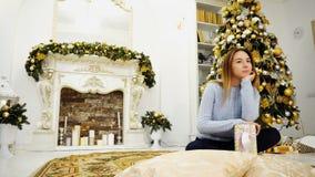Mooi Meisje in Nieuwjaarstemming met Gift het in Hand Glimlachen bij Camera Royalty-vrije Stock Afbeeldingen